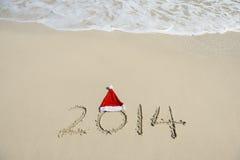 2014 avec le bonhomme de neige de Santa sur le sable de plage de mer Images stock