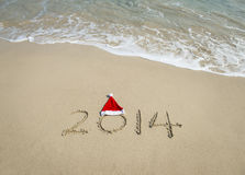 2014 avec le chapeau de Santa sur le sable de plage de mer Images stock