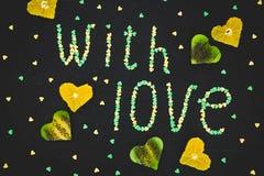 ` Avec le ` d'amour fait de fruit de confettis et de kiwi sur le fond noir Concept d'amour Configuration plate, vue supérieure Images libres de droits