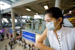 Avec le masque de grippe à l'aéroport Image libre de droits