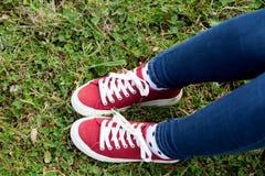 Avec les espadrilles rouges et les jeans marchant l'herbe Photo stock