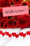 Avec les souhaits d'amour et le bouquet des roses rouges magnifiques Images libres de droits
