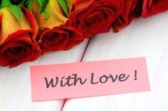 Avec les souhaits d'amour et le bouquet des roses rouges magnifiques Image libre de droits