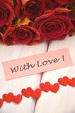 Avec les souhaits d'amour et le bouquet des roses rouges magnifiques Photos stock