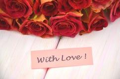 Avec les souhaits d'amour et le bouquet des roses rouges magnifiques Photos libres de droits
