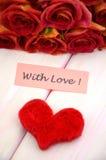 Avec les souhaits d'amour et le bouquet des roses rouges magnifiques Image stock