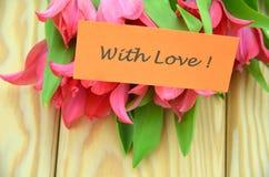 Avec les souhaits d'amour et le bouquet des tulipes rouges magnifiques Image stock