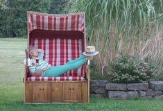 Avec Stetson comme protection solaire ses pieds, une boisson et un suncream rouge ainsi la femme attirante apprécie le jour dans  image stock