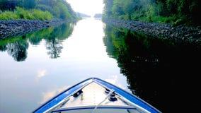 Avec un bateau sur une rivière suédoise Image stock