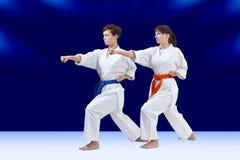 Avec une ceinture orange et la ceinture bleue les sportives battent le bras de poinçon Photographie stock