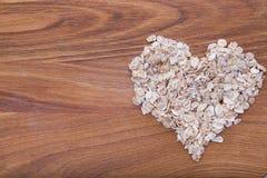 A aveia lasca-se em uma forma do coração Fotos de Stock