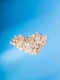 A aveia saudável do café da manhã do cereal lasca-se em uma forma do coração, Foto de Stock Royalty Free