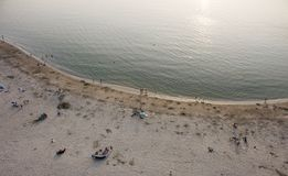 Aveiro, Portugal - Agosto 2018: Aerial view of peaceful Barra Beach with few people. Gentle waves and sun glare in water stock photo