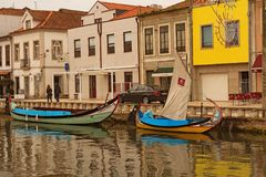 Typical landscape view of ancient city Aveiro. Moored colorful boat near embankment with small old houses stock photography