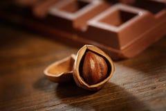 Avelã com a barra de chocolate na tabela de madeira rústica Imagem de Stock