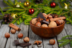 Avelã e nozes com chocolate e canela em uma bacia de madeira imagem de stock