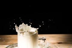 Avellana en chapoteo de la leche Descensos en una tabla de madera Fotos de archivo libres de regalías
