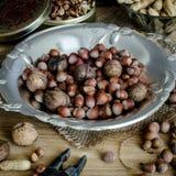 Avellanas, cacahuetes, nueces en una tabla de madera Imagen de archivo