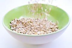 Avena del porridge che versa nella ciotola Fotografie Stock