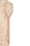 Avena-escamas con una cuchara de madera Foto de archivo libre de regalías