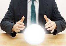 Avenir de prévision d'homme d'affaires de diseur de bonne aventure avec de la boule de cristal Images stock