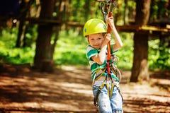Aventúrese el parque del cable de alta tensión que sube - pequeño niño en curso en casco de la montaña y el equipo de seguridad imagenes de archivo