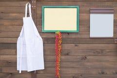 Avental branco na parede com quadro para seu texto Fotografia de Stock Royalty Free