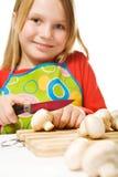 Avental desgastando da menina que corta cogumelos Foto de Stock Royalty Free