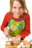 Avental desgastando da menina que corta cogumelos Foto de Stock