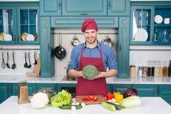 Avental do desgaste do cozinheiro chefe do homem que cozinha na cozinha Receita do vegetariano do cozinheiro do homem com legumes imagem de stock royalty free