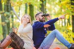 A aventura come?a agora Os pares no amor relaxam na floresta do outono com ch? ou caf? vinho surpreendido da bebida da menina bea imagem de stock royalty free