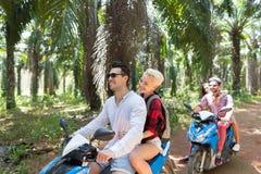 Aventura el vacaciones: Dos pares jovenes en viaje de la vespa en el grupo de personas tropical de Forest Together On Bike Happy Fotos de archivo libres de regalías