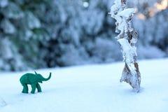 Aventura verde del elefante de la plastilina con la planta congelada en nieve Fotografía de archivo libre de regalías