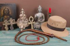 Aventura y concepto arqueológico para los artefactos perdidos con el sombrero, azote, florero antiguo del hierro, imagen santa, l Imágenes de archivo libres de regalías