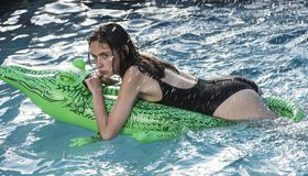 Aventuras da menina no crocodilo Relaxe na piscina luxuosa mulher no mar com colchão inflável Férias de verão fotos de stock royalty free