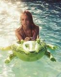 Aventuras de la muchacha en cocodrilo aventuras y el viajar de la muchacha con el cocodrilo inflable foto de archivo libre de regalías