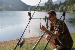 Aventuras de la pesca, pesca de la carpa El pescador está preparando el equipo imágenes de archivo libres de regalías