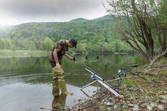 Aventuras de la pesca, pesca de la carpa Pescador con las botas de goma verdes imagen de archivo libre de regalías
