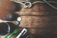 Aventuras exteriores - artigos de acampamento da expedição no fundo de madeira imagem de stock