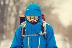 Aventureiro no óculos de proteção e capa durante o blizzard imagens de stock