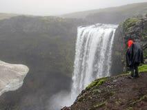 Aventurero adulto masculino del caminante que camina en el impermeable que retrocede al aire libre mirando la cascada en el viaje foto de archivo