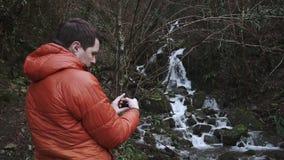 Aventurero con smartphone en un bosque almacen de metraje de vídeo
