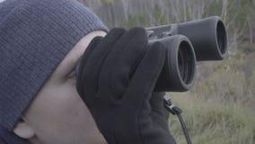 Aventurero del cazador del hombre joven que mira a través de los prismáticos cerca encima de la cara metrajes