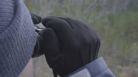 Aventurero del cazador del hombre joven que mira a través de los prismáticos cerca para arriba almacen de metraje de vídeo