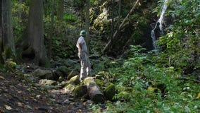 Aventurero en el bosque cerca de la cascada almacen de video