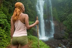 Aventurero femenino que mira la cascada Fotografía de archivo libre de regalías