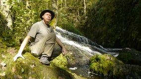 Aventurero que se sienta al lado de una cascada almacen de metraje de vídeo