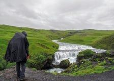Aventurier adulte masculin de randonneur trimardant dans l'imperméable reculant extérieur regardant la cascade dans le voyage de  photographie stock