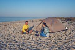 Aventuriers, avec un petit chien drôle, détendant sur la plage Photos libres de droits