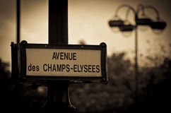 Avenue des Champs-Elysees, Paris. Avenue des Champs-Elysees road sign on a lamp post in Paris in sepia royalty free stock photo